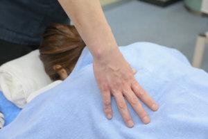 患者の背中に手を当てている先生